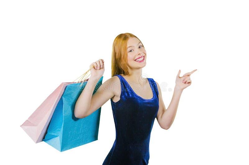 Śliczna miedzianowłosa dziewczyna w błękitnej aksamit sukni z torbami nad jej ramieniem pokazuje z jej palcem wskazującym strona  obraz royalty free