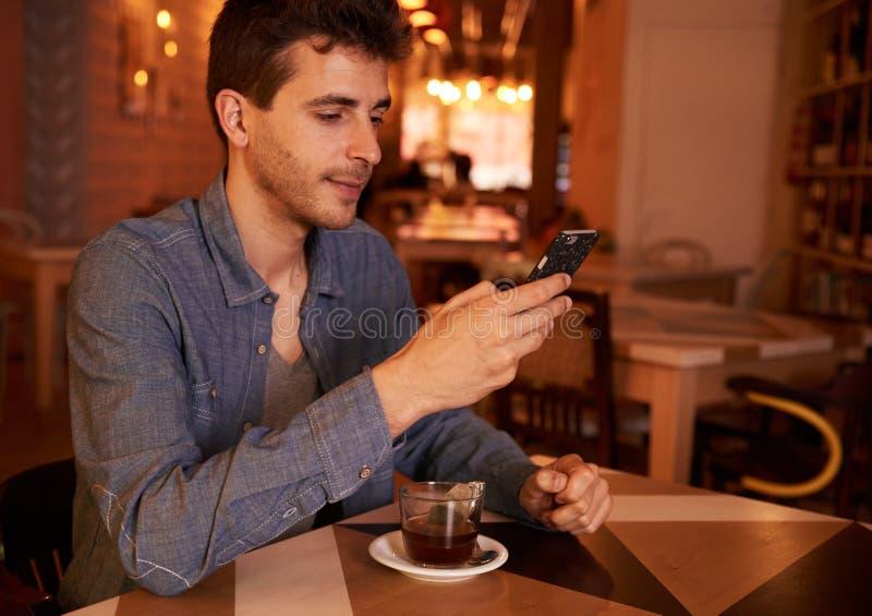 Śliczna millenial samiec texting w restauraci obrazy royalty free