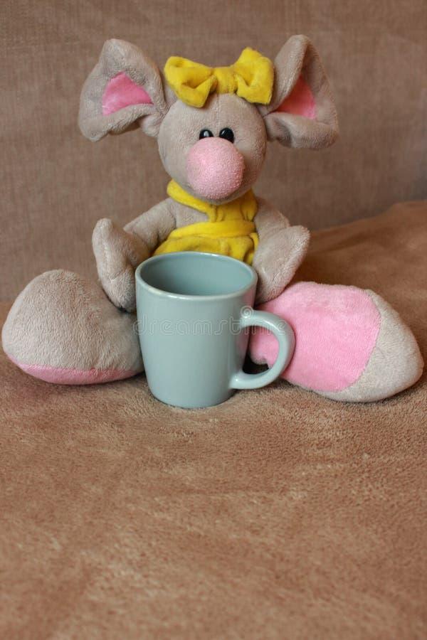 Śliczna myszy zabawka z herbacianej filiżanki obsiadaniem na kanapie Miękka zwierzę zabawka Dnia dobrego pojęcie Dzieciństwa tło  zdjęcia stock