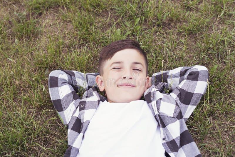 Śliczna nastolatek chłopiec relaksuje w parku zdjęcie royalty free
