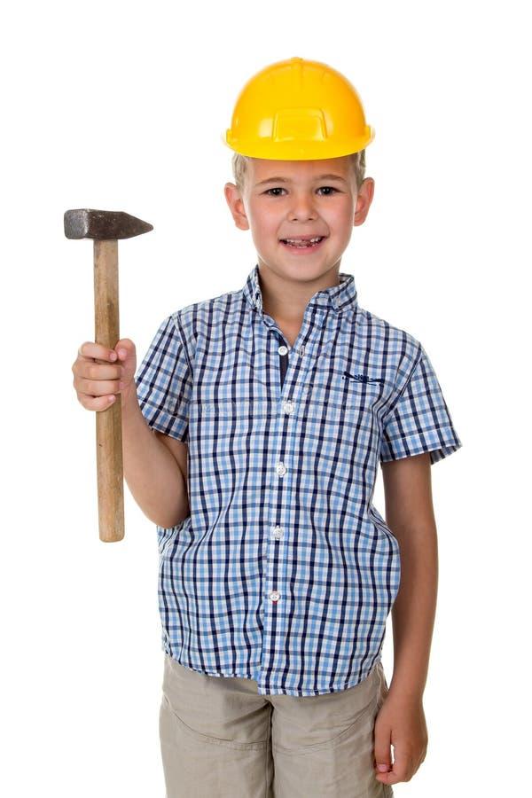 Śliczna nastolatek chłopiec w błękitnym w kratkę koszula i koloru żółtego budynku hełmie, mienie młot na białym odosobnionym tle fotografia royalty free