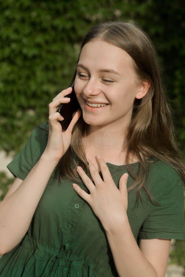 Śliczna nastolatek dziewczyna opowiada outdoors i ono uśmiecha się na telefonie komórkowym Komunikacja i edukacja obrazy stock