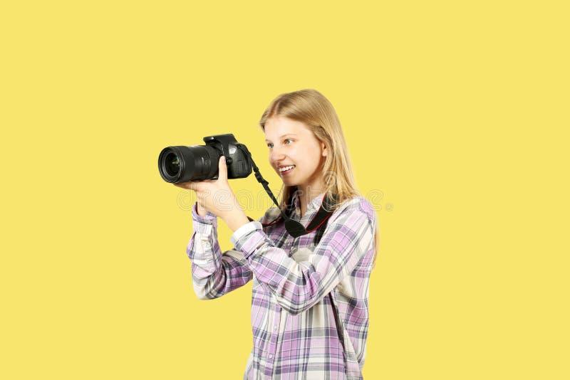 Śliczna nastolatek dziewczyna pozuje z cyfrową SLR fotografii kamerą, ogromny teleobiektyw, troczący jej szyja Odosobniony Żółty  zdjęcia stock