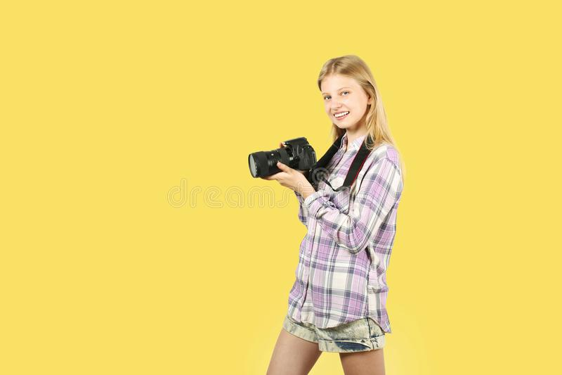 Śliczna nastolatek dziewczyna pozuje z cyfrową SLR fotografii kamerą, ogromny teleobiektyw, troczący jej szyja Odosobniony Żółty  zdjęcia royalty free