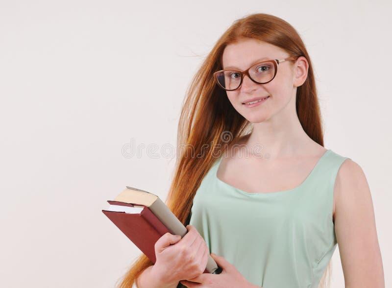 Śliczna nastolatek dziewczyna w szkłach z długą czerwoną włosianą pozycją i mieniu książki obrazy stock