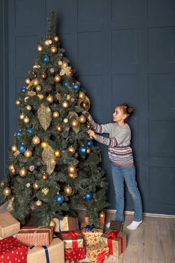 Śliczna nastoletnia dziewczyna w pulowerze i cajgach z śmieszną fryzurą dekoruje Bożenarodzeniowe piłki z nowego roku drzewem obrazy royalty free