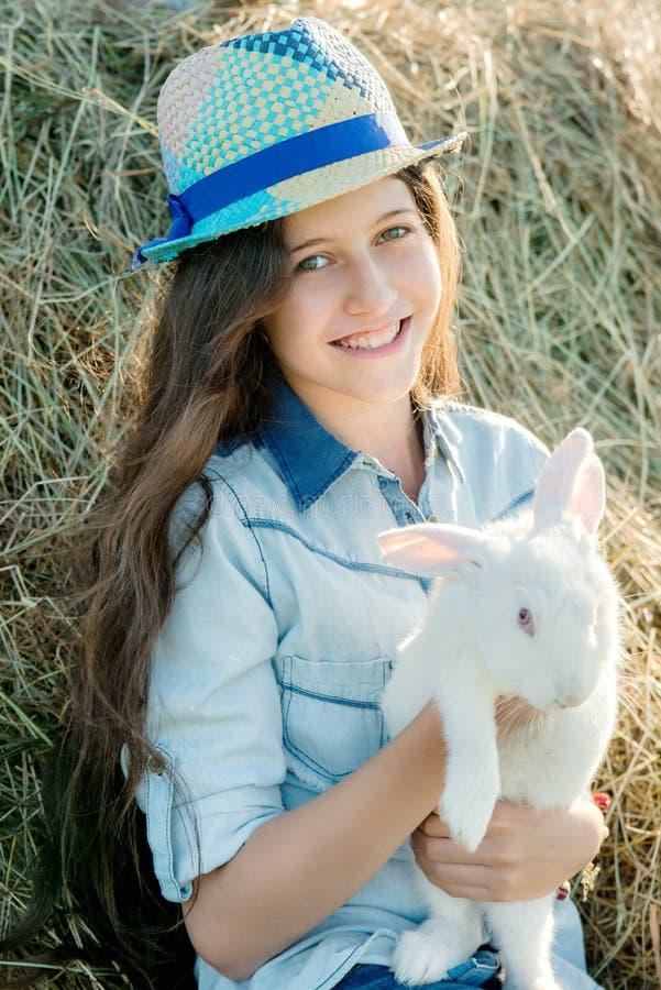 Śliczna nastoletnia dziewczyna z białym królika obsiadaniem przed haystack obrazy royalty free