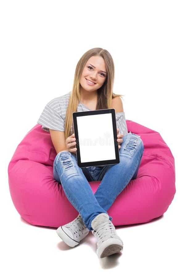 Śliczna nastoletnia studencka dziewczyna pokazuje pastylkę z bielu ekranem fotografia stock