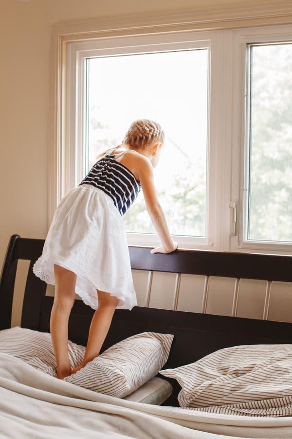 Śliczna płetwista biała Kaukaska blondynki dziewczyna na łóżku w domu obrazy royalty free