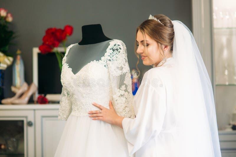 Śliczna panna młoda ubierał w domu w ślubnej sukni zdjęcie royalty free
