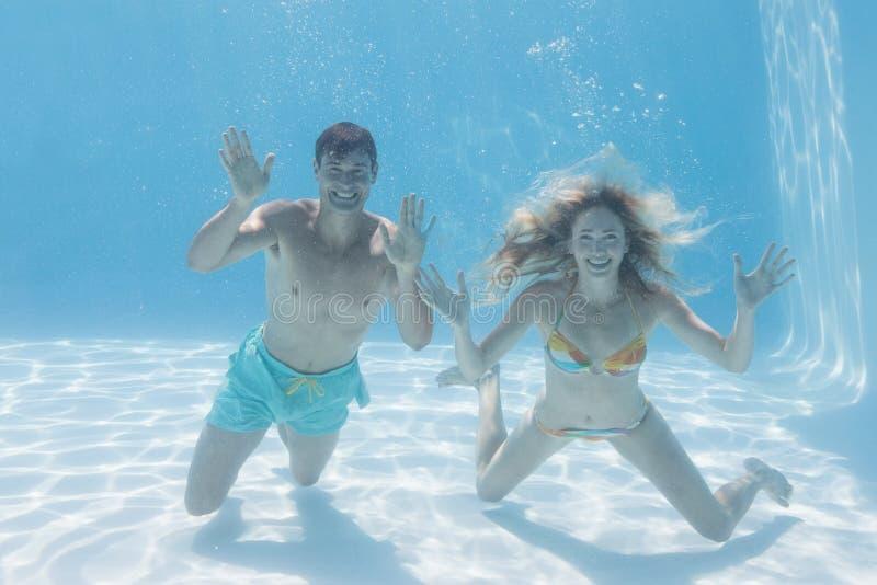 Śliczna para ono uśmiecha się przy kamerą podwodną w pływackim basenie zdjęcia royalty free