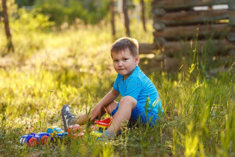 Śliczna pięcioletnia chłopiec w błękitów ubraniach bawić się z samochodami w lata obsiadaniu na trawie zdjęcie royalty free