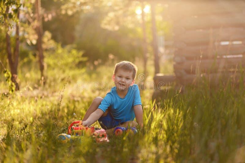 Śliczna pięcioletnia chłopiec w błękitnej koszulce i skrótach bawić się z plastikowymi samochodami w lata obsiadaniu na trawie w  zdjęcie stock