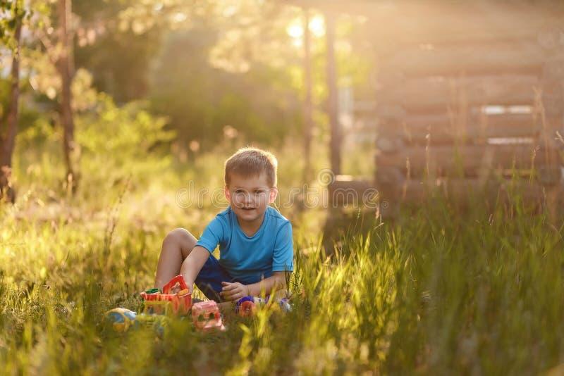 Śliczna pięcioletnia chłopiec w błękitnej koszulce i skrótach bawić się z samochodami w lata obsiadaniu na trawie w ciepłym świet zdjęcia stock