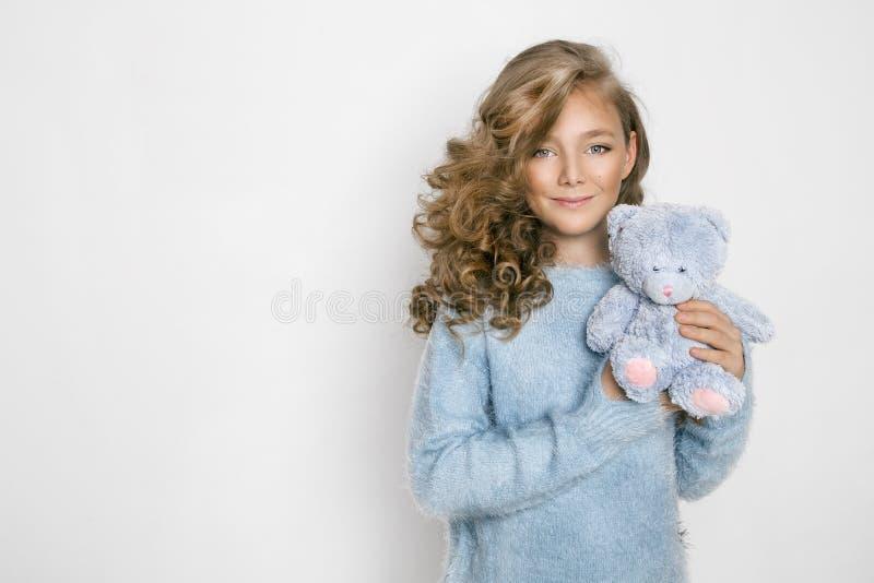 Śliczna, piękna blondynki młoda dziewczyna z zadziwiającym włosy, trzyma misia obrazy stock