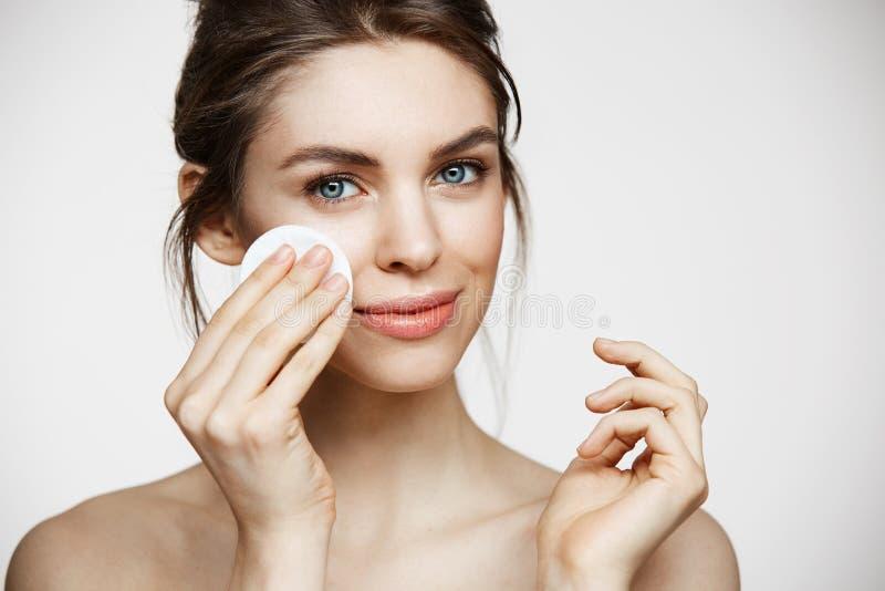 Śliczna piękna naturalna brunetki dziewczyny cleaning twarz z bawełnianą gąbką ono uśmiecha się patrzejący kamerę nad białym tłem obrazy stock
