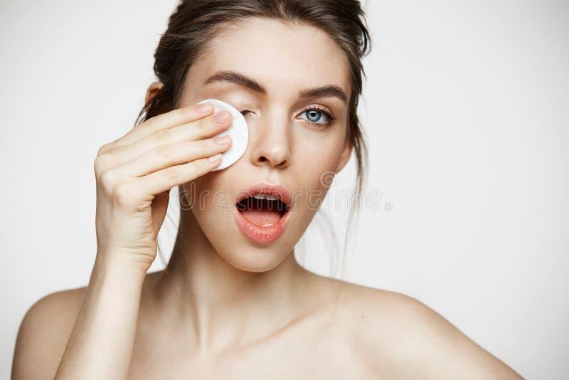 Śliczna piękna naturalna brunetki dziewczyny cleaning twarz z bawełnianą gąbką ono uśmiecha się patrzejący kamerę nad białym tłem obrazy royalty free