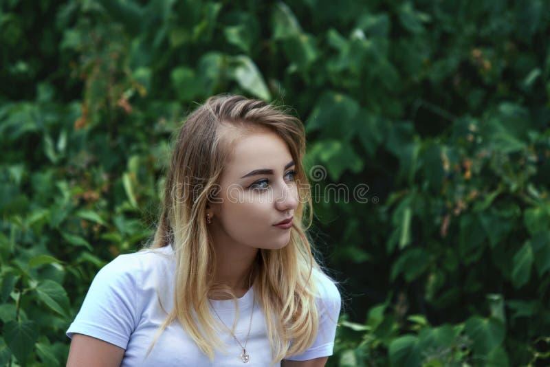 Śliczna powabna blondynka w bluzki białych spojrzeniach w odległość o obrazy royalty free