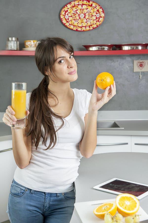 Śliczna powabna kobieta robi sokowi i je pomarańcze obraz royalty free