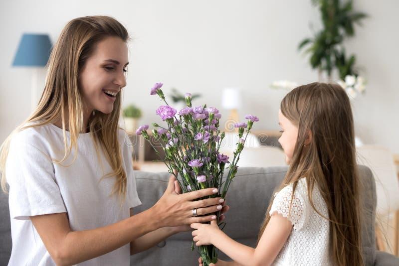 Śliczna preschool córka daje macierzyści kwiaty zdjęcie stock