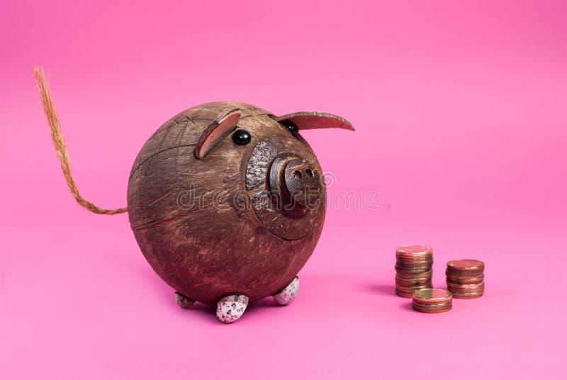 Śliczna prosiątko metalu i banka moneta odizolowywająca na różowym tle fotografia royalty free