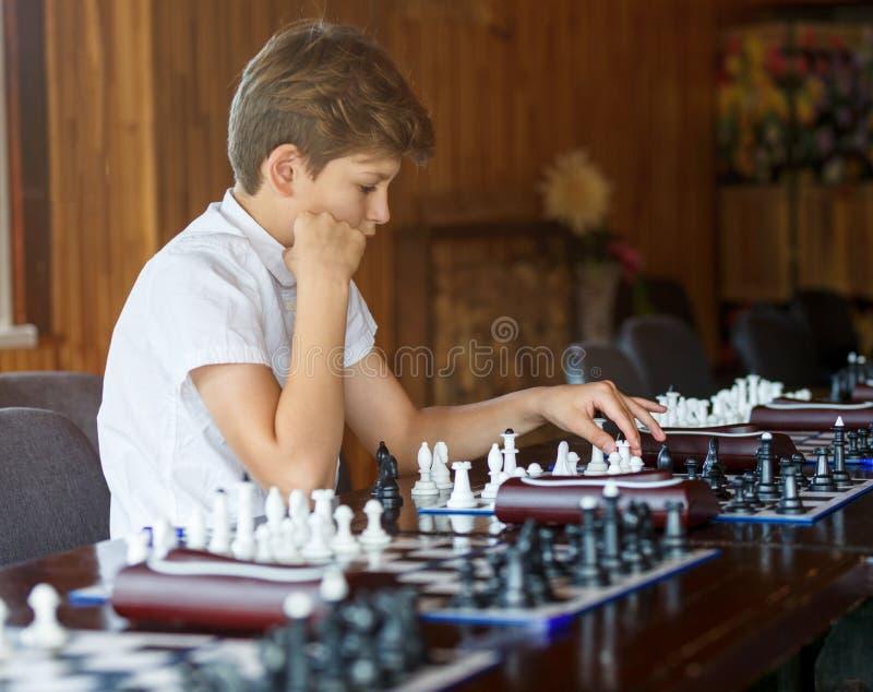 Śliczna przystojna chłopiec w białej t koszula bawić się szachy z jego rywalem w szachy klasie Edukacji pojęcie, intelektualna gr zdjęcia royalty free
