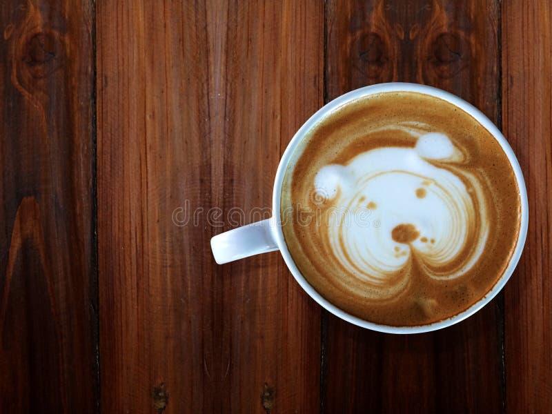 Śliczna psia twarzy latte sztuki kawa w białej filiżance na drewnianym stole zdjęcia stock