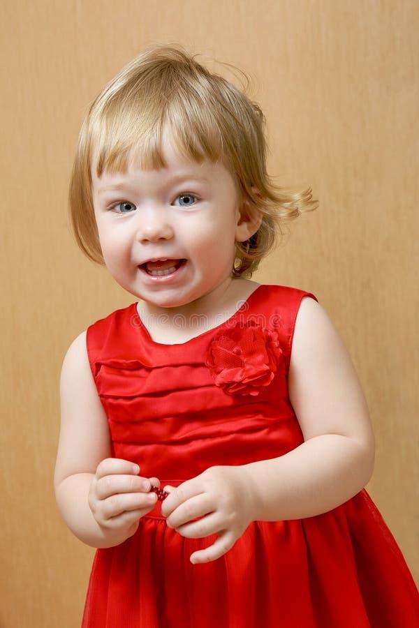 Śliczna roześmiana dziewczyna w czerwieni sukni zdjęcia stock