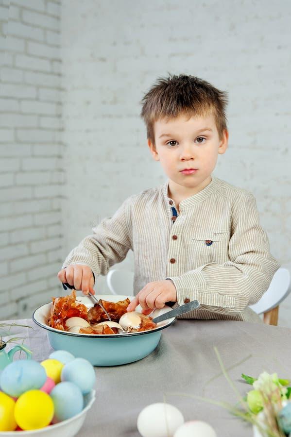 Śliczna serius chłopiec maluje Wielkanocnych jajka na białym tle obrazy royalty free