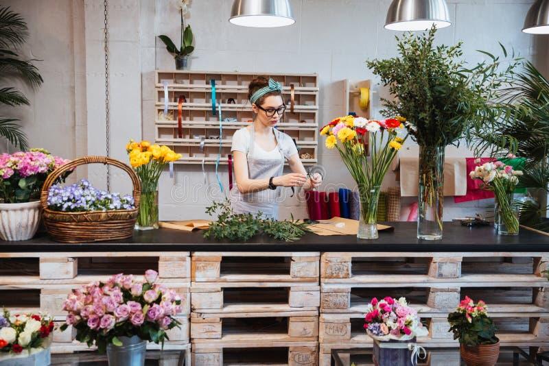 Śliczna skoncentrowana żeńska kwiaciarnia pracuje w kwiatu sklepie obrazy stock