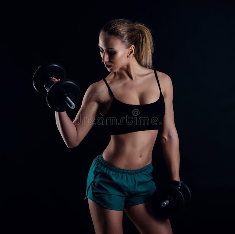 Śliczna sportowa wzorcowa dziewczyna w sportswear z dumbbells w studiu przeciw czarnemu tłu Idealna kobieta sportów postać zdjęcia stock