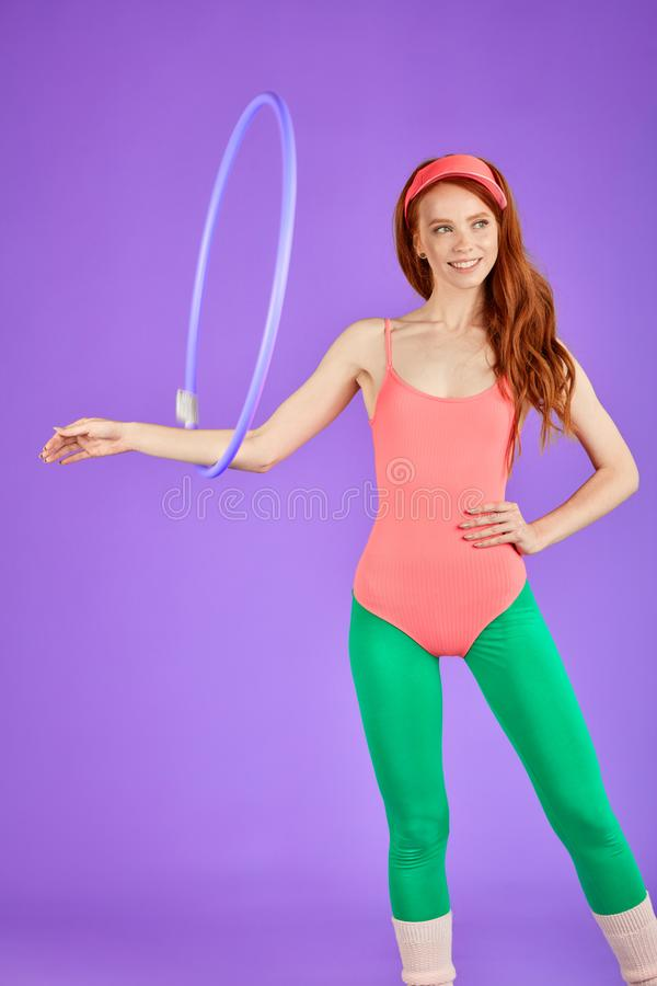Śliczna studencka dziewczyna z długim kędzierzawym czerwonym włosy robi ćwiczeniom z hula obręczem w sprawności fizycznej klasie zdjęcie royalty free