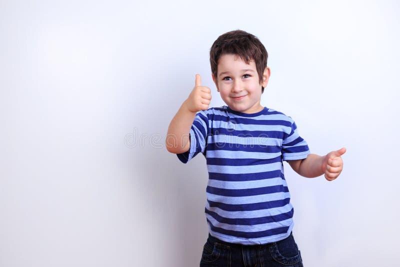 Śliczna szczęśliwa chłopiec pokazuje aprobaty, pracowniany krótkopęd na bielu emocja zdjęcia stock