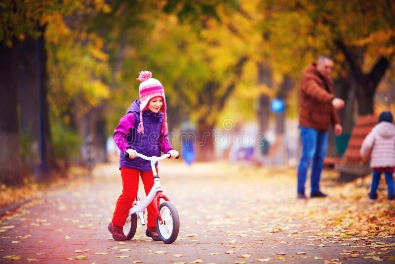Śliczna szczęśliwa dziewczyna jedzie rower na jesieni ulicie obrazy royalty free