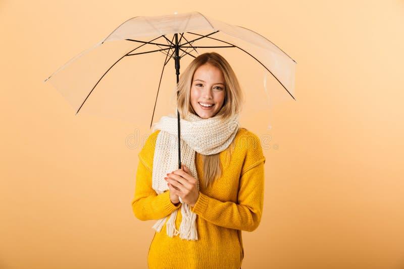 Śliczna szczęśliwa kobieta jest ubranym szalika mienia parasola pozować odizolowywam nad kolor żółty ściany tłem obraz royalty free