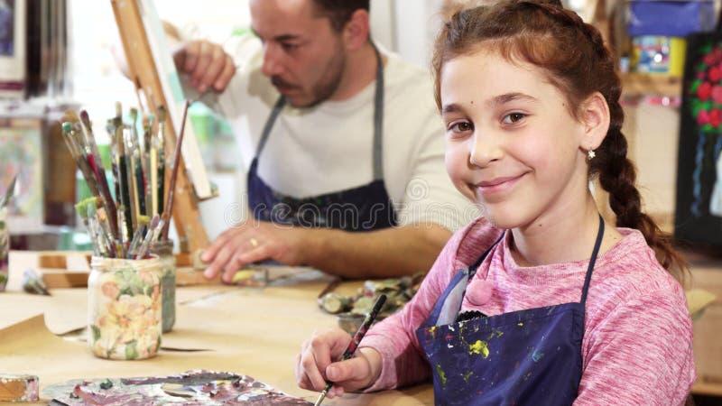 Śliczna szczęśliwa litlle dziewczyna ono uśmiecha się kamera podczas gdy rysujący obrazek obraz royalty free
