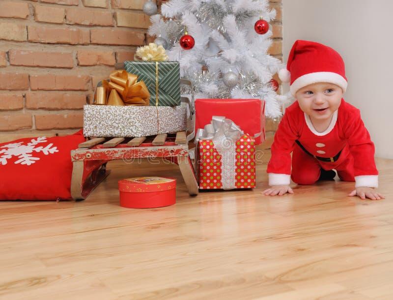 Śliczna szczęśliwa mała chłopiec w Santa kostiumu i starych rocznika sania wi obraz stock