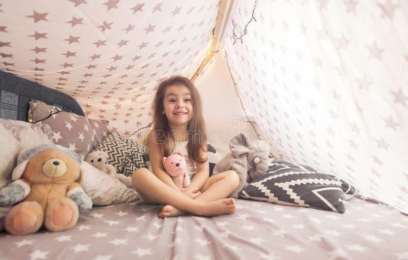 Śliczna szczęśliwa mała dziewczynka bawić się z zabawkami i marzy w teepee i łóżku obrazy royalty free