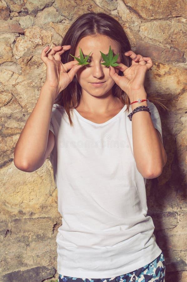 Śliczna szczupła kobieta z bezprawnymi konopi liśćmi przy jej oczami zdjęcia stock