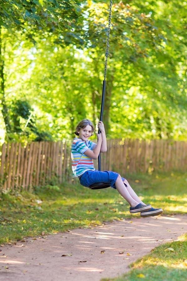 Śliczna szkolna chłopiec cieszy się huśtawkową przejażdżkę na boisku zdjęcie royalty free