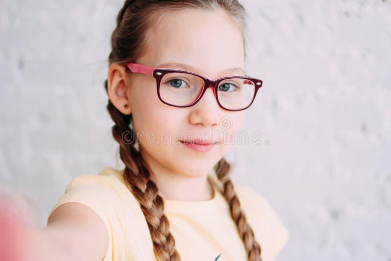 Śliczna tweens dziewczyna w żółtej koszulce z śmiesznymi pigtails bierze selfie na czołowej kamerze na białym ściany z cegieł tle obrazy stock