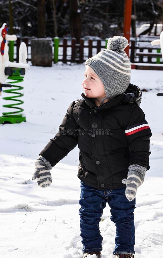 Śliczna uśmiechnięta chłopiec bawić się z śniegiem zdjęcie royalty free