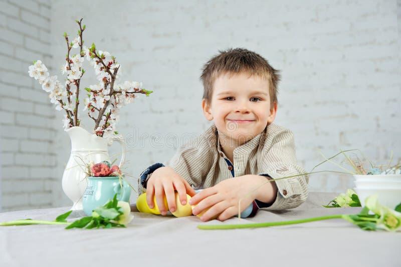 Śliczna uśmiechnięta chłopiec maluje Wielkanocnych jajka na białym tle zdjęcia stock