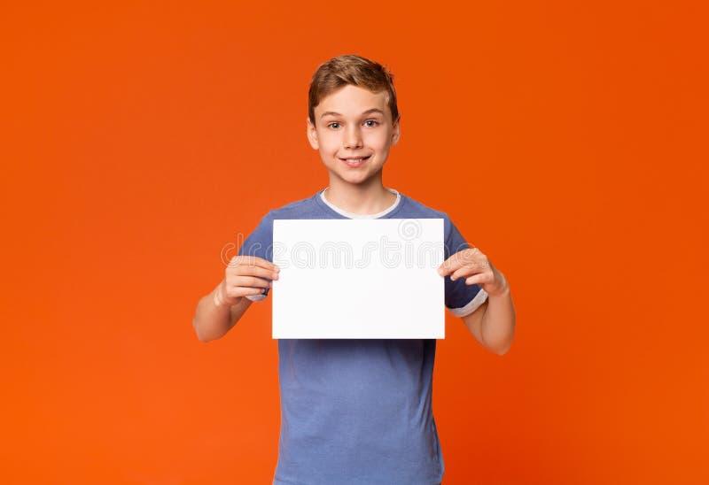 Śliczna uśmiechnięta chłopiec trzyma białego pustego plakat obrazy stock
