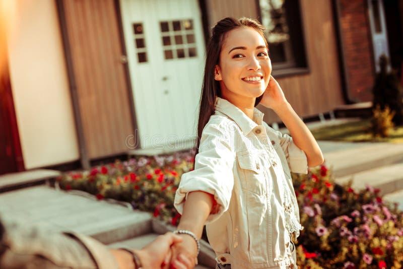 Śliczna uśmiechnięta ciemnowłosa dziewczyna w białej kurtce pokazuje białych zęby zdjęcie royalty free