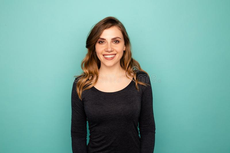 Śliczna uśmiechnięta dama w studiu pozuje na kamerze odizolowywającej zdjęcie stock