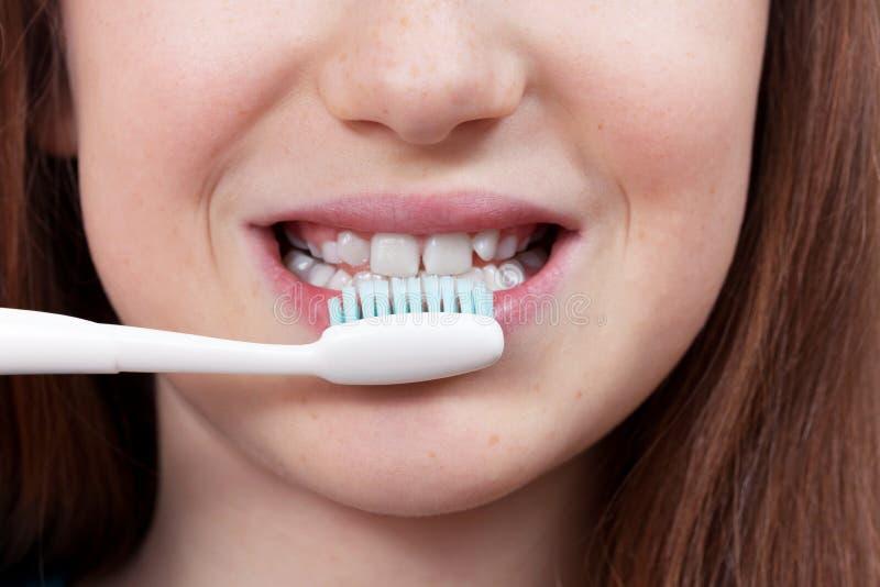 Śliczna uśmiechnięta dziewczyna szczotkuje jej zęby zdjęcia royalty free