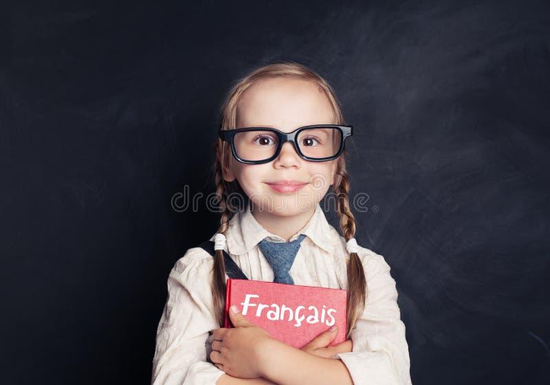 Śliczna uśmiechnięta dziewczyna z francuz książką w językowej szkoły sala lekcyjnej zdjęcia royalty free