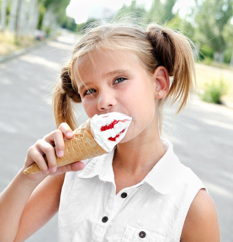 Śliczna uśmiechnięta mała dziewczynka je lody zdjęcia royalty free