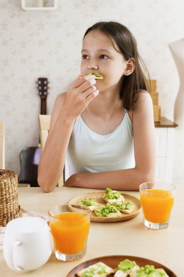 Śliczna uśmiechnięta preteen dziewczyna ma zdrowego śniadanie: avocado sok pomarańczowy i kanapka Zdrowy stylu życia pojęcie, jar obraz royalty free